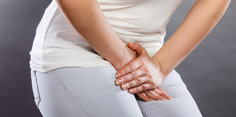 Woman with hands holding pressing her crotch lower abdomen