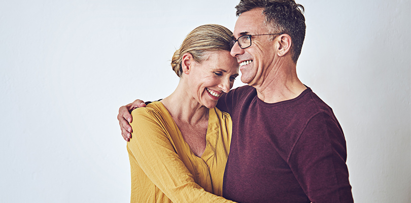 Older man and woman standing with arms around each other