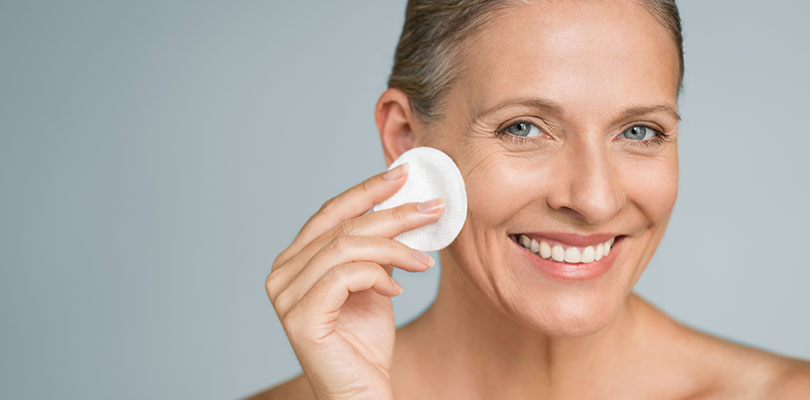 Beauty portrait of happy woman cleaning skin and looking at camera