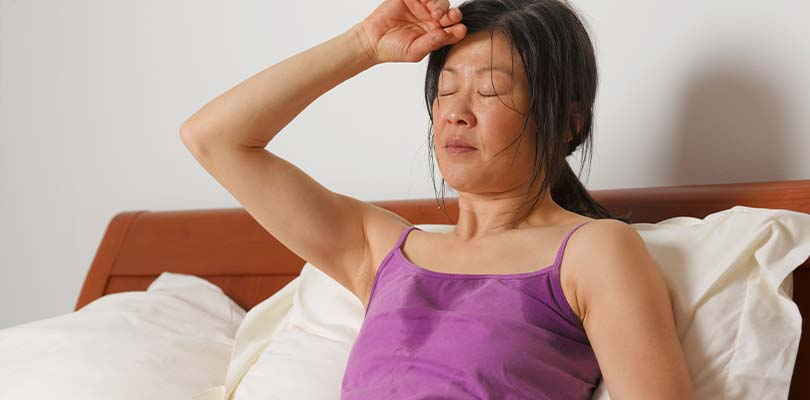 A woman in a pink tank top experiencing a hot flash.